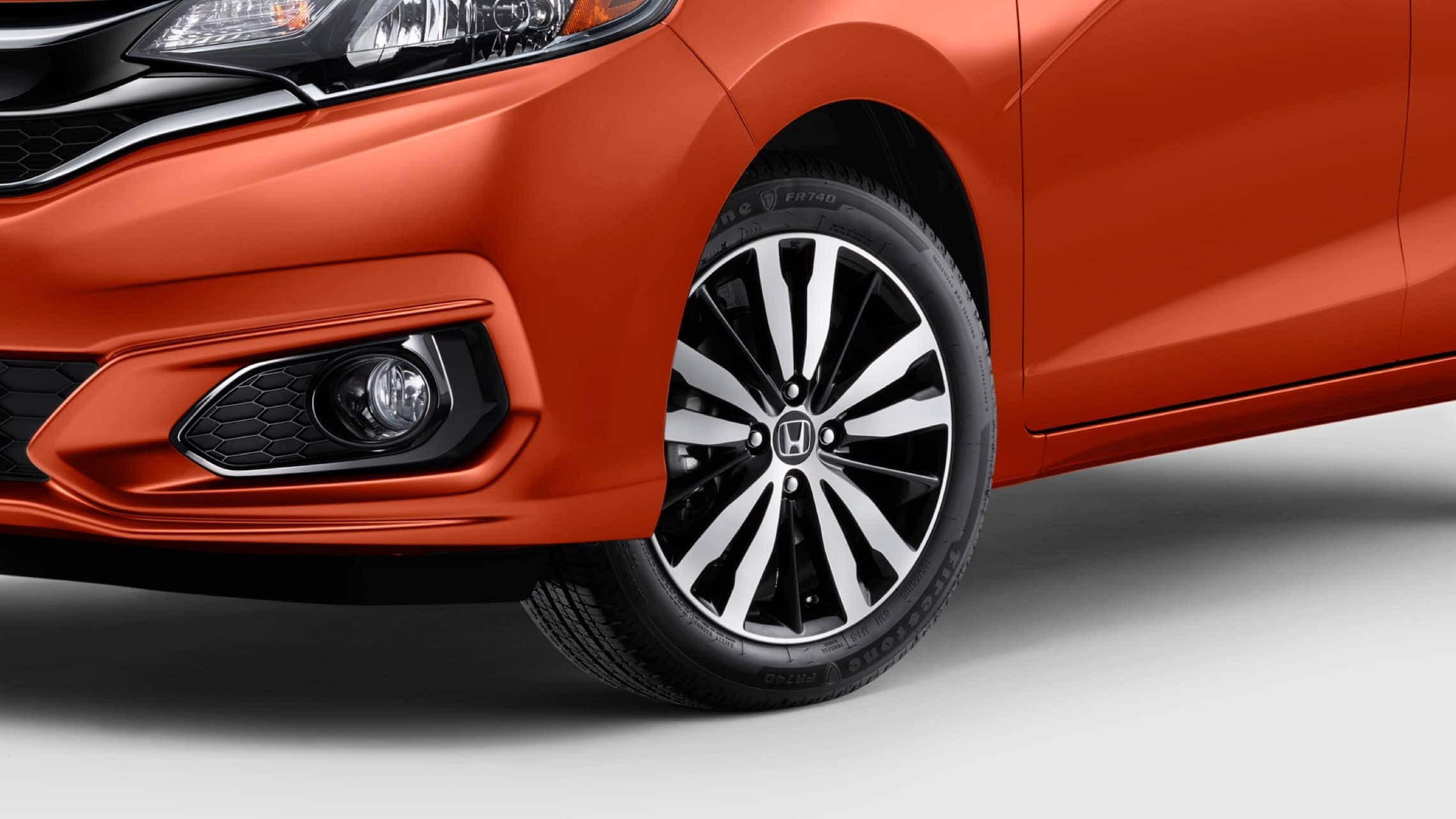 Driver side 3/4 view of 16-inch alloy wheel detail on 2019 Honda Fit EX-L in Orange Fury.