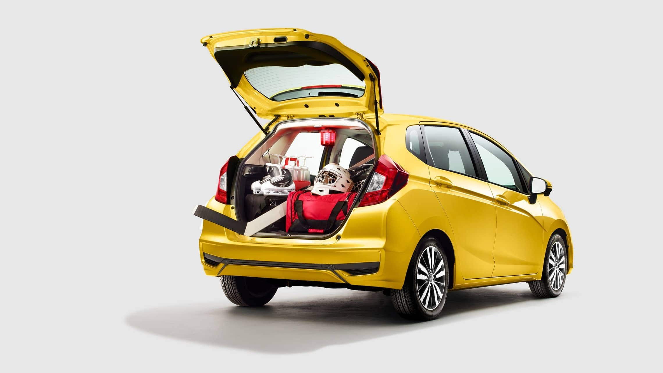 Rear 3/4 passenger side view of 2019 Honda Fit EX-L in Helios Yellow Pearl with liftgate open with Honda Genuine Accessories in cargo area.
