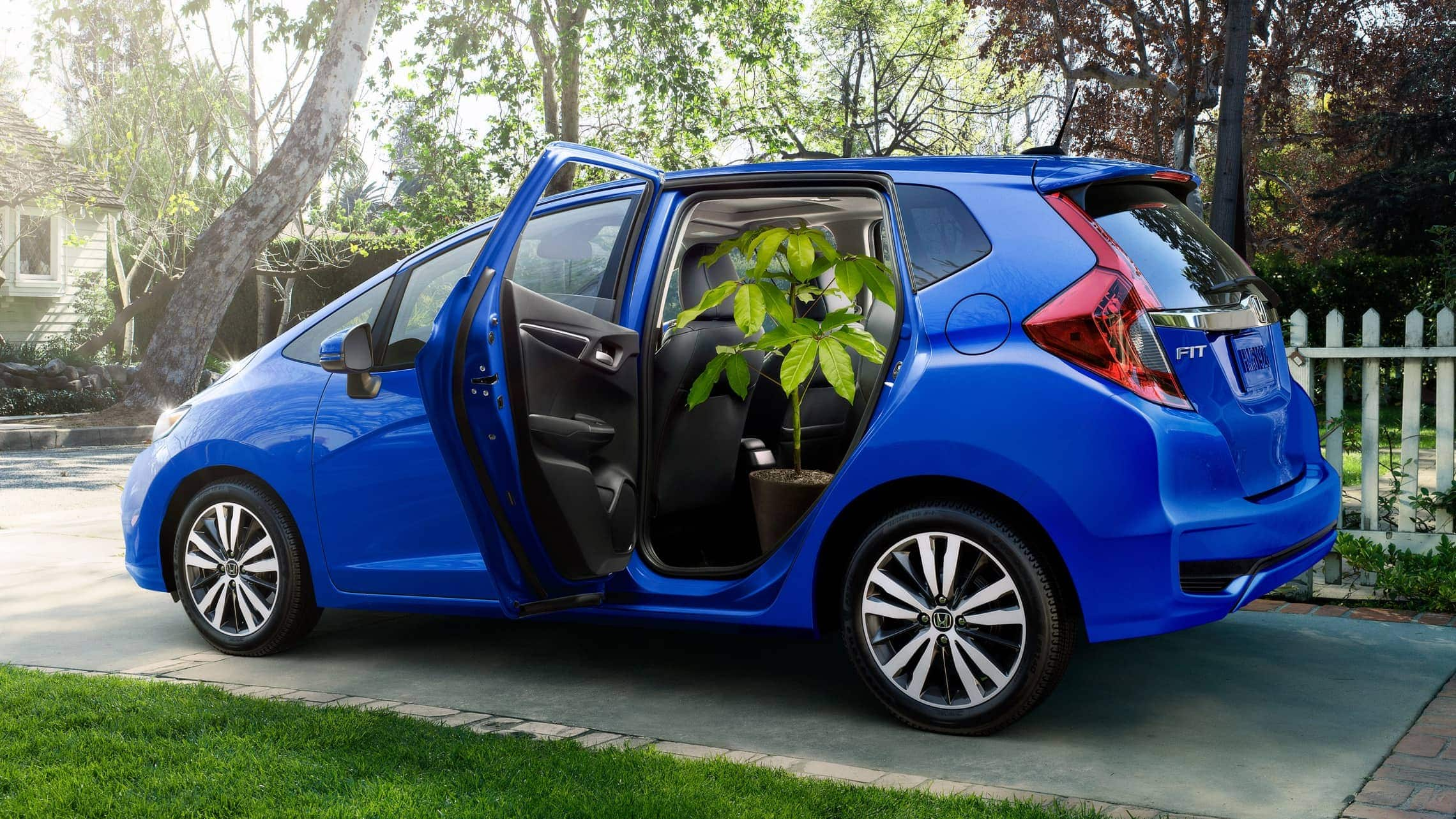 7/8 rear passenger side view of 2019 Honda Fit EX-L in Aegean Blue Metallic with 2nd-row Magic Seat® folded up for Honda Genuine Accessories.
