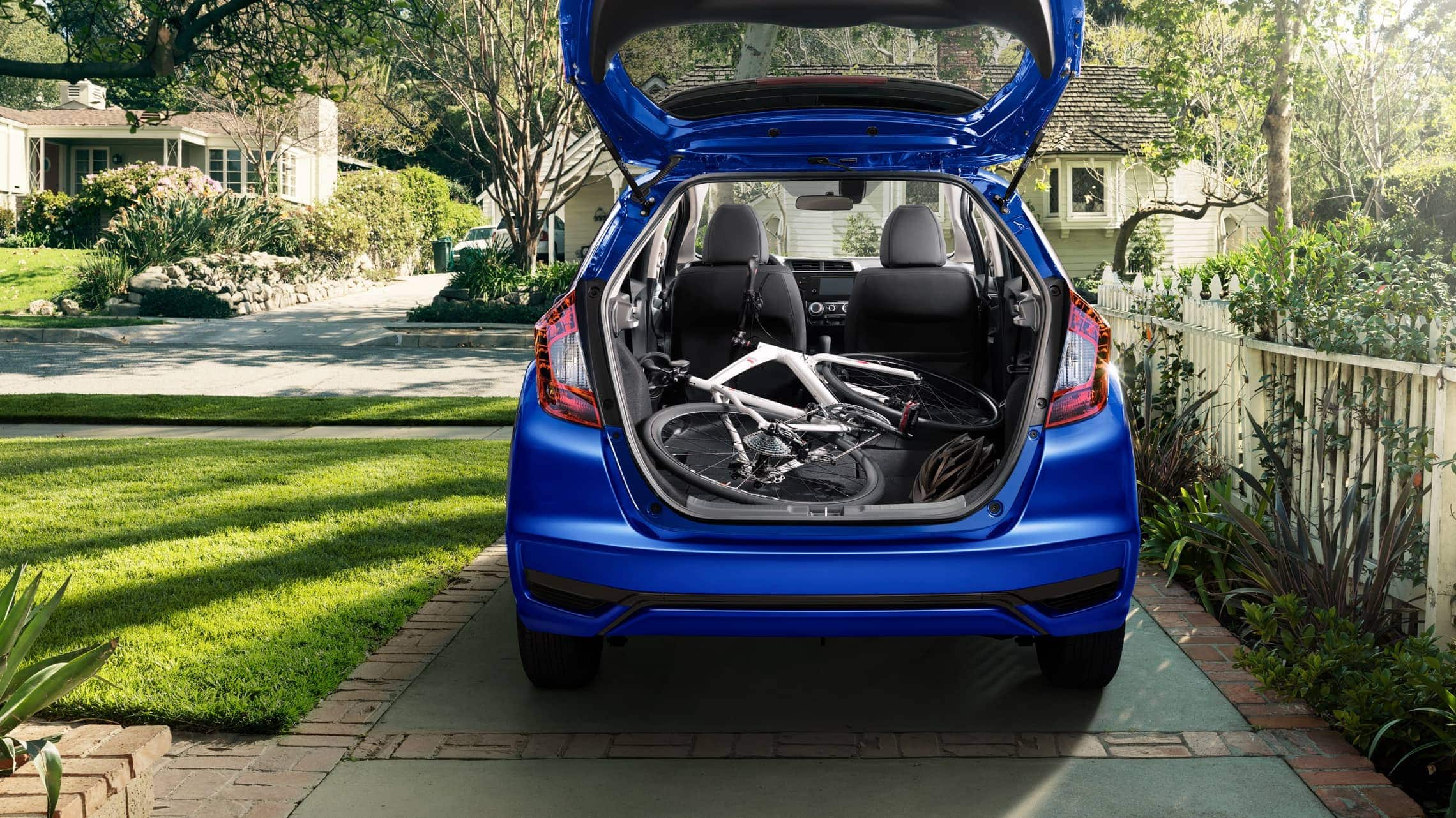 Exterior rear view of 2019 Honda Fit EX-L in Aegean Blue Metallic with open liftgate holding Honda Genuine Accessories.