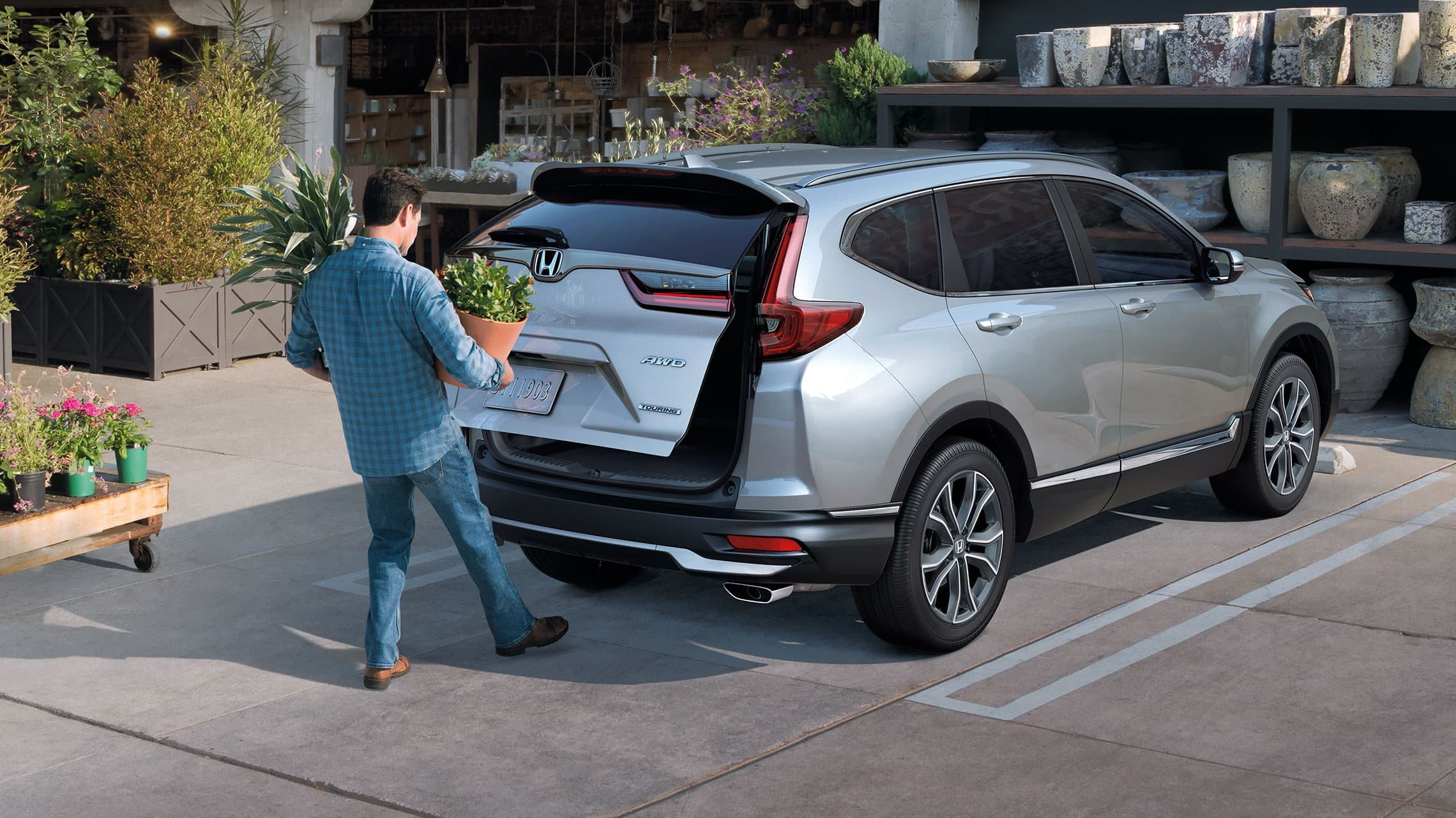 Rear 3/4 passenger-side view of 2020 Honda CR-V Touring in Lunar Silver Metallic demonstrating hands-free access power tailgate.