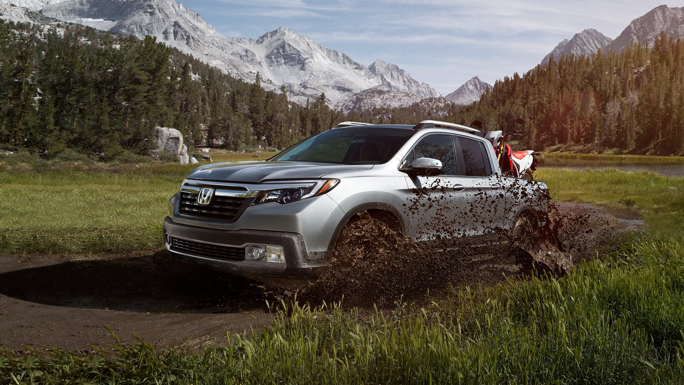 Front driver-side view of the 2020 Honda Ridgeline RTL-E in Lunar Silver Metallic driving through mud, storing dirt bikes in truck bed.
