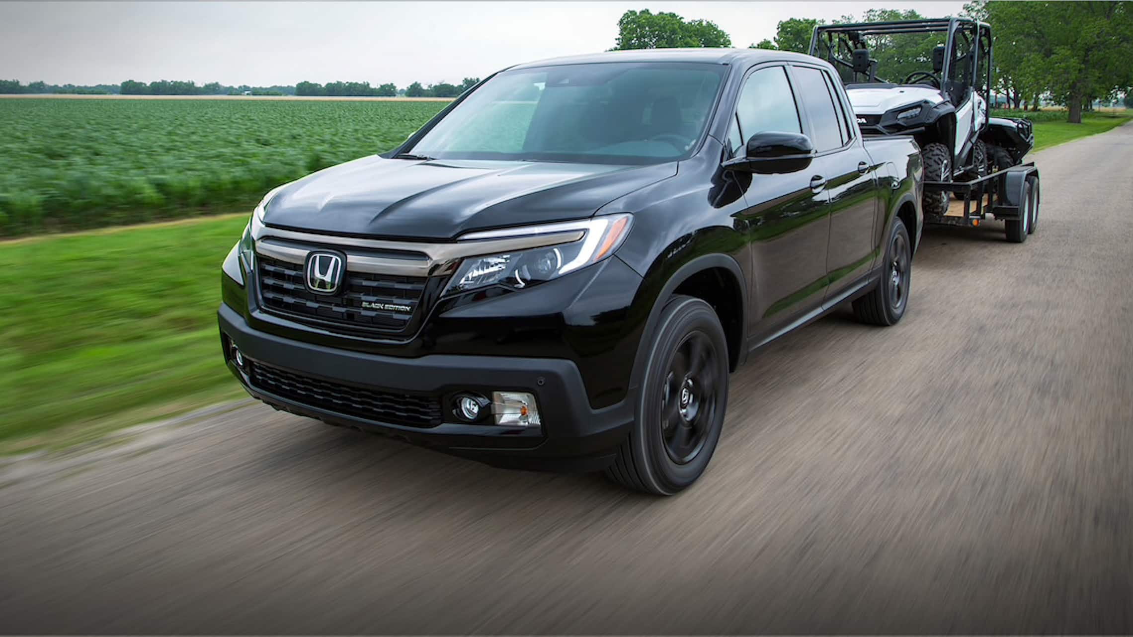 Rear view of the 2020 Honda Ridgeline RTL-E in Lunar Silver Metallic driving through dirt road, storing two dirt bikes in truck bed.