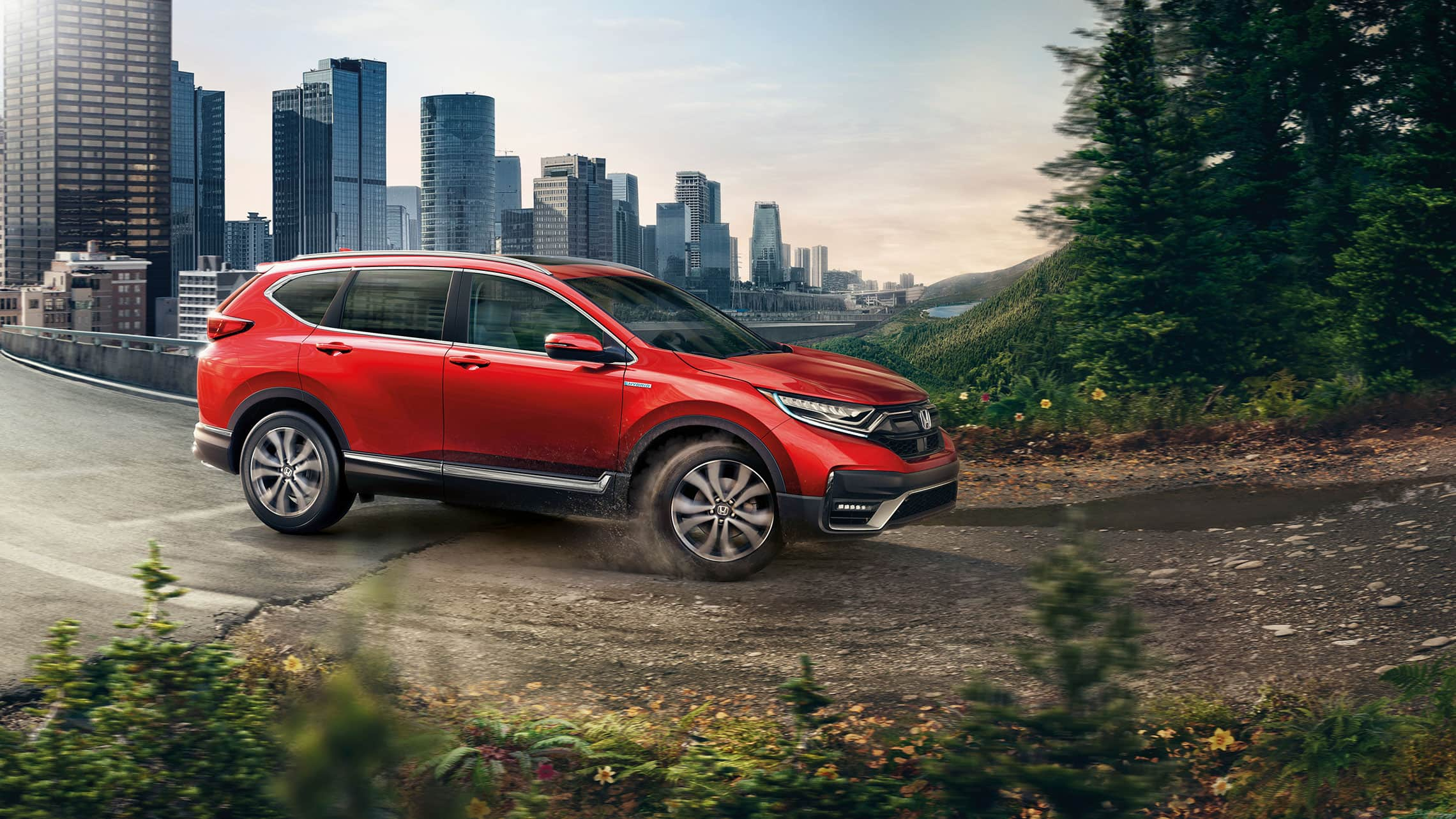 Passenger-side view of the 2021 CR-V Hybrid Touring with AWD in Radiant Red Metallic, driving from a city into a forest.