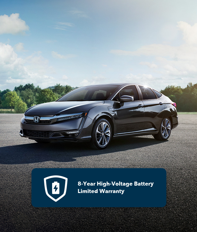 Front of 2021 Clarity Plug-In Hybrid in Modern Steel Metallic driving on highway along lake.