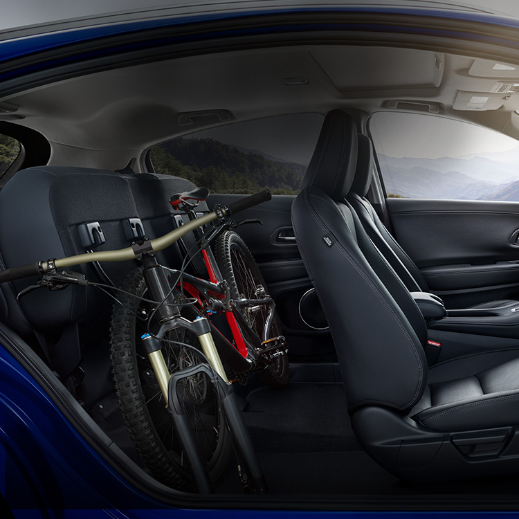 Interior passenger-side view of the 2021 Honda HR-V EX-L with Black Leather, with rear seats folded down, stowing a bike.